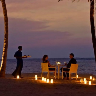 Beach dinner setup with a couple and waiter serving. Candled walkway to the table at the sunset hour at Sun Aqua Pasikudah
