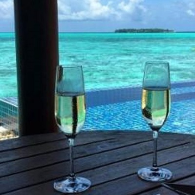 02 glasses of champagne on a table over seeing a infinity pool over a turquoise lagoon in Maldives