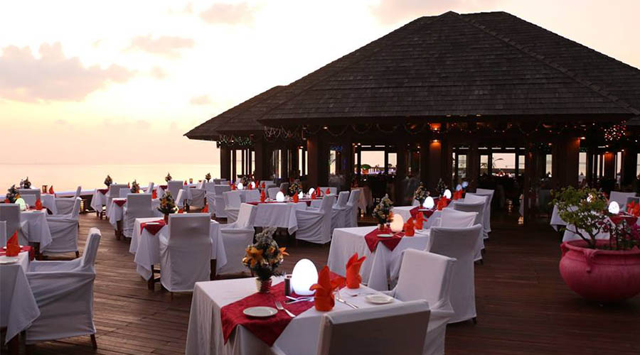 Valentines day dinner set up tables at an over water venue at sunset