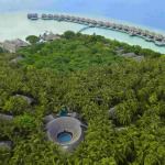 drone image of Dusit International property in maldives. With lush green and over water villas above the turquoise waters