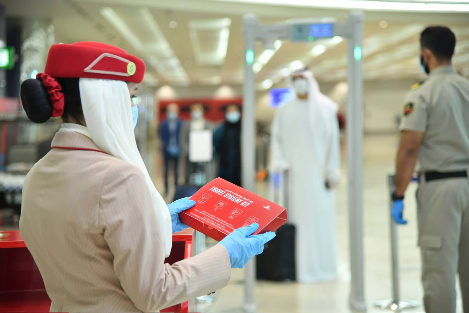 Emirates dubai airport staff holding a red package for a passenger