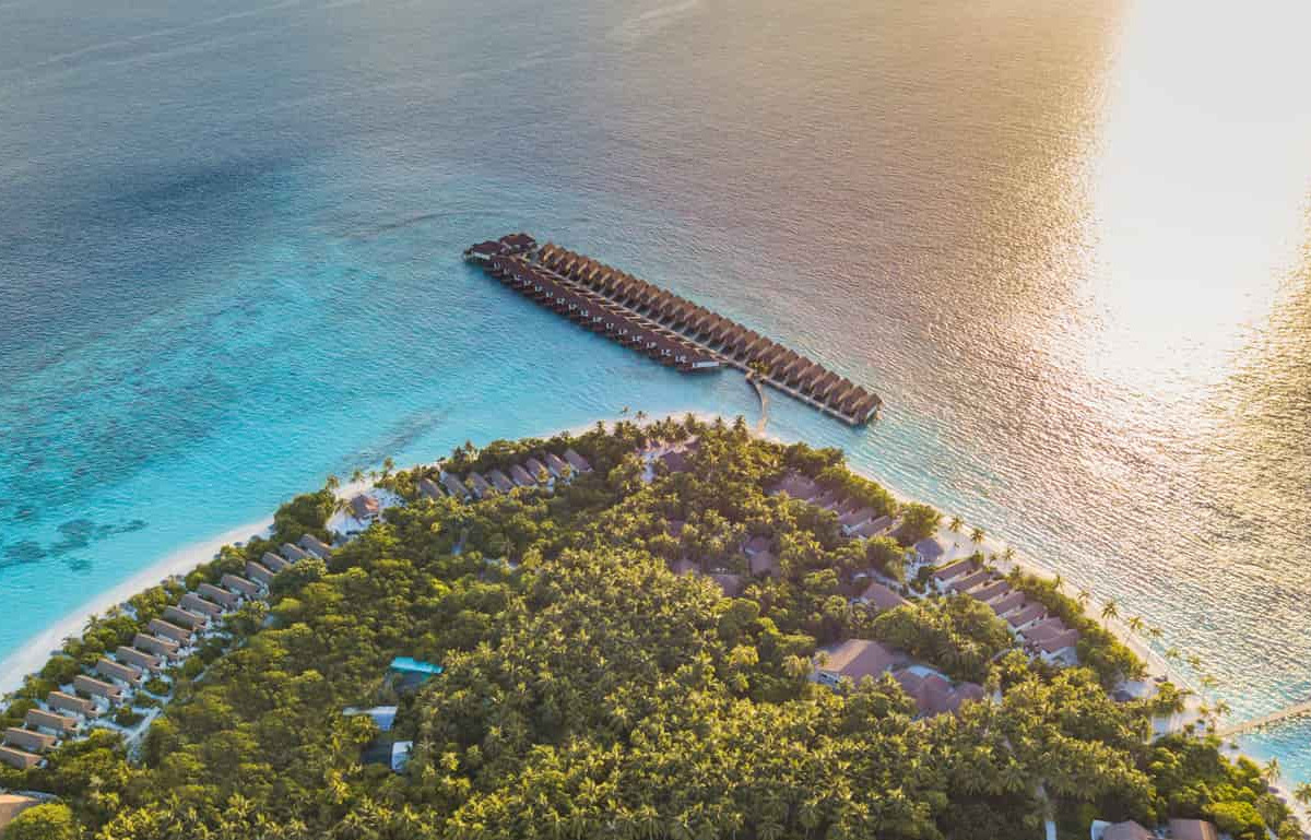 Drone image of Reethi Faru Resort. lish green trees , white sandy beaches and crystal clear waters