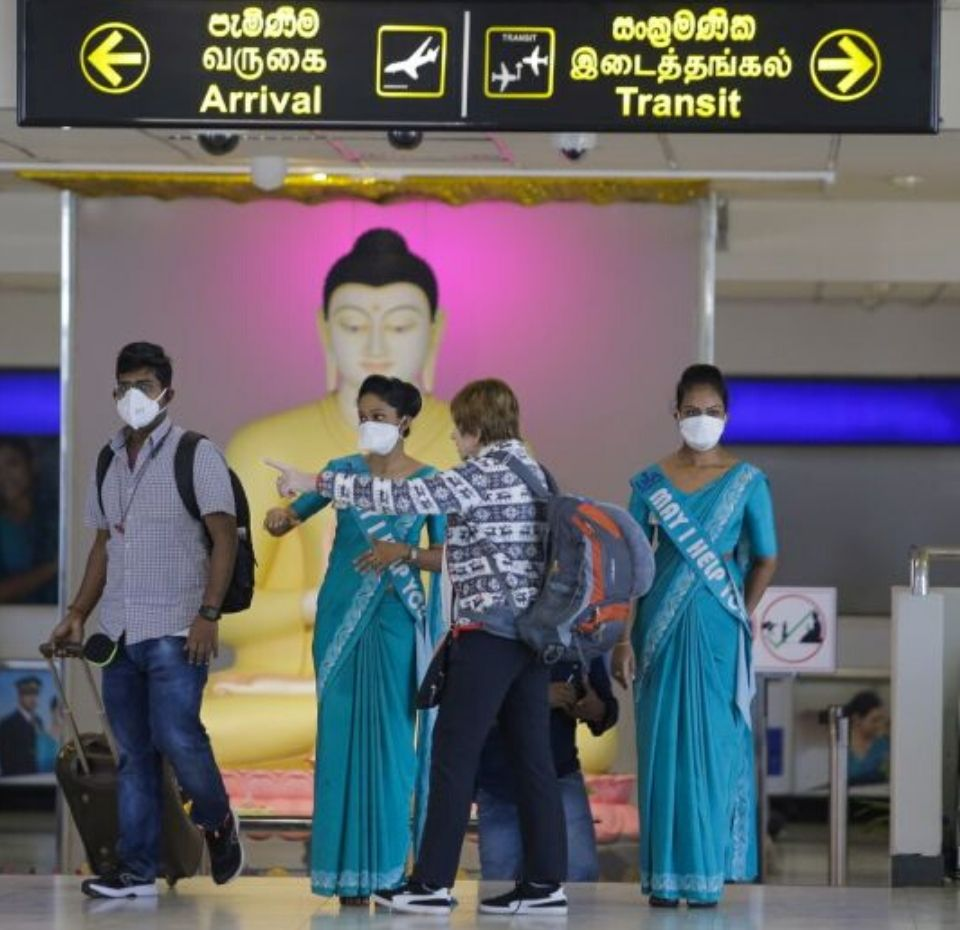 Colombo airport official with masks on directing passengers to there request