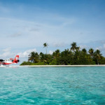 Trans Maldivian Airways aircraft in ready to take off from a turquoise lagoon in Maldives.