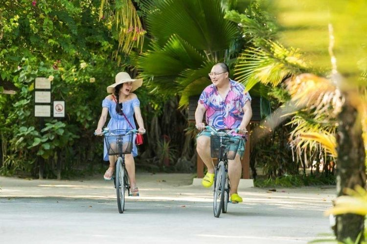 couple riding bike in the greenery of a Maldives Resort
