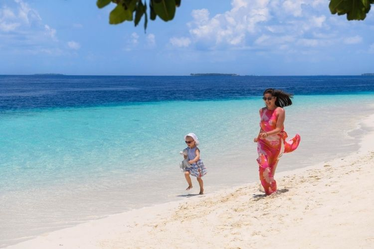 family enjoying holiday on the beach at Emerald Maldives Resort & Spa