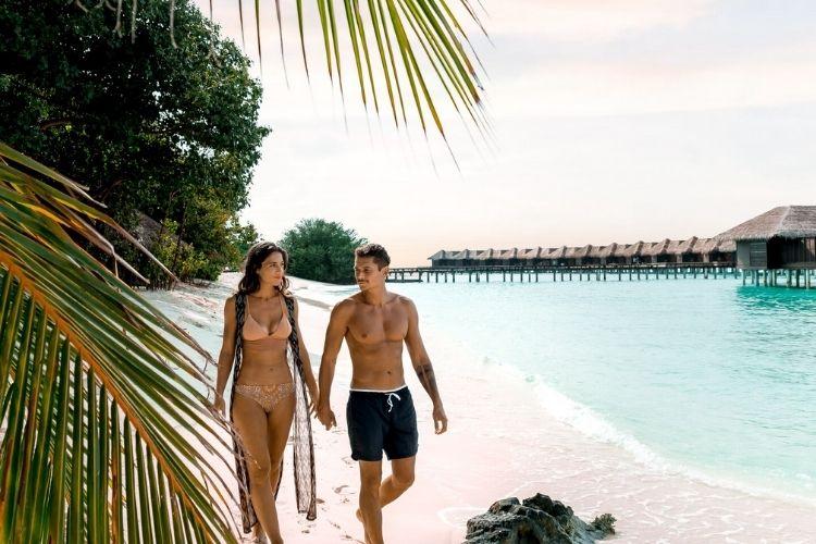 tourists enjoying a beach walk in the Maldives